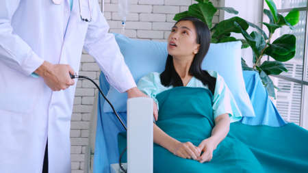 Doctor in professional uniform examining patient at hospital or medical clinic. Health care , medical and doctor staff service concept.