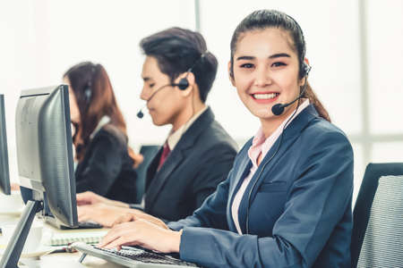 Business people wearing headset working in office to support remote customer or colleague. Call center, telemarketing, customer support agent provide service on telephone video conference call. Standard-Bild