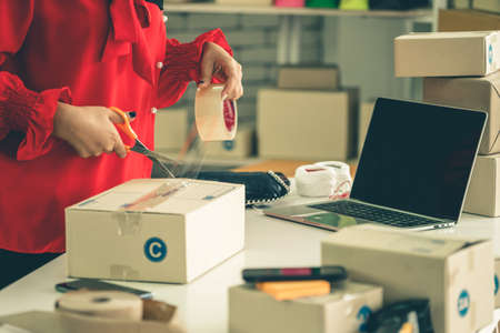 Online seller works at home office and packs shipping delivery box to customer. Small business owner or entrepreneur doing e-commerce business on the internet.