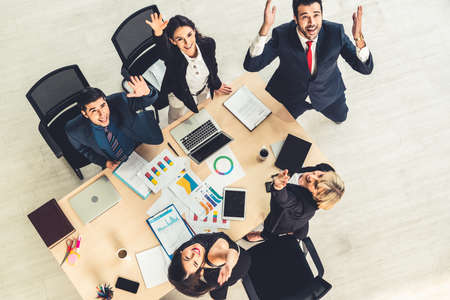 Successful business people celebrate together with joy at office table shot from top view . Young businessman and businesswoman workers express cheerful victory showing success by teamwork .