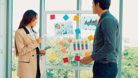 Business people work on project planning board in office and having conversation with coworker friend to analyze project development . They use sticky notes posted on glass wall to make it organized .