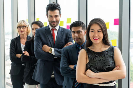 Successful business people standing together showing strong relationship of worker community. A team of businessman and businesswoman expressing a strong group teamwork at the modern office. 스톡 콘텐츠
