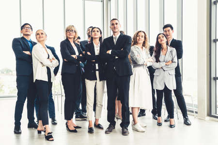 Successful business people standing together showing strong relationship of worker community. A team of businessman and businesswoman expressing a strong group teamwork at the modern office. Banque d'images