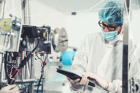 Production line worker with face mask working in electronic factory . Concept of protective action and quarantine to stop spreading of Coronavirus Disease 2019 or COVID-19 .