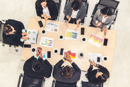Successful business people celebrate together with joy at office table shot from top view . Young businessman and businesswoman workers express cheerful victory showing success by teamwork . Stockfoto