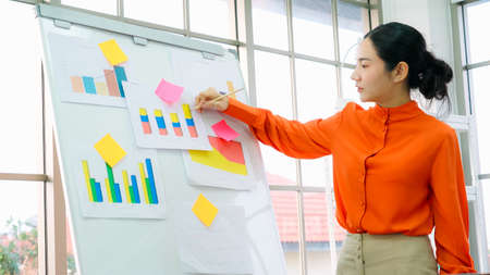 Young woman explains business data on white board in casual office room . The confident Asian businesswoman reports information progress of a business project to partner to determine market strategy . Banco de Imagens