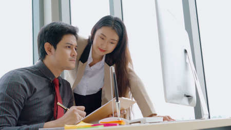 Two business people talk project strategy at office meeting room. Businessman discuss project planning with colleague at modern workplace while having conversation and advice on financial data report.