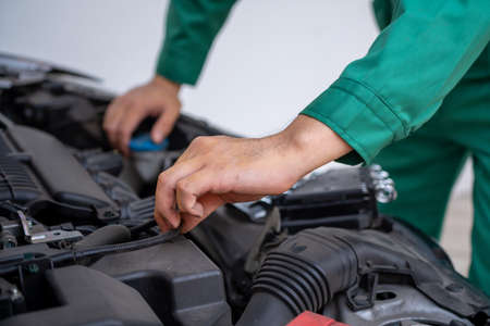 Professional mechanic hand providing car repair and maintenance service in auto garage. Car service business concept.