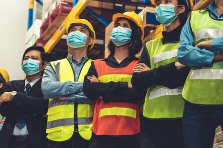 Group of factory industry worker working with face mask to prevent Covid-19 Coronavirus spreading during job reopening period .