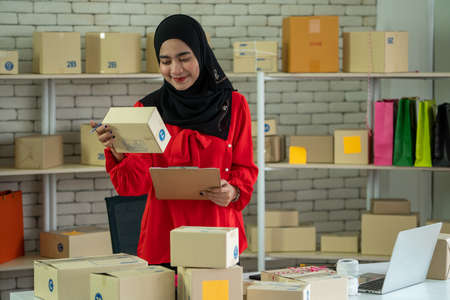 Muslim online seller at home office with shipping box for delivery to customer. Small business owner or entrepreneur doing e-commerce business on the internet.