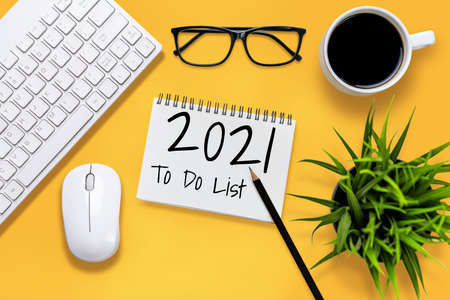 2021 Happy New Year Resolution Goal List - Business office desk with notebook written in handwriting about plan listing of new year goals and resolutions setting. Change and determination concept. Imagens