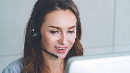 Business people wearing headset working in office to support remote customer or colleague. Call center, telemarketing, customer support agent provide service on telephone video conference call. Imagens