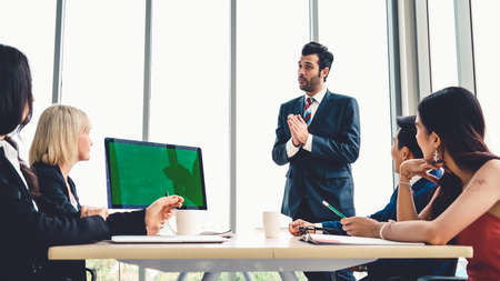 Business people in the conference room with green screen chroma key TV or computer on the office table. Diverse group of businessman and businesswoman in meeting on video conference call . Imagens
