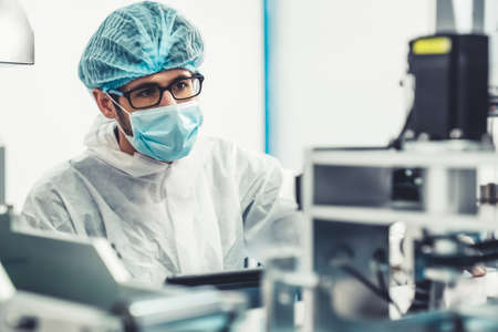 Production line worker with face mask working in electronic factory . Concept of protective action and quarantine to stop spreading of Coronavirus Disease 2019 or COVID-19 . Stock Photo