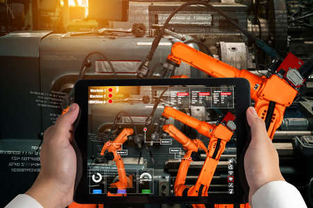 Engineer controls robotic arms by augmented reality industry technology application software. Smart robot machine in future factory working in concept of Industry 4.0 or 4th industrial revolution. Archivio Fotografico