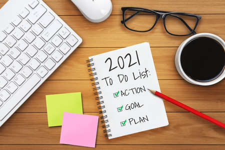 2021 Happy New Year Resolution Goal List - Business office desk with notebook written in handwriting about plan listing of new year goals and resolutions setting. Change and determination concept. Stock Photo