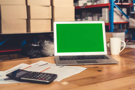 Computer with green screen display in warehouse storage room . Delivery and transportation software concept . Standard-Bild