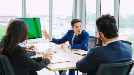 Business people in the conference room with green screen chroma key TV or computer on the office table. Diverse group of businessman and businesswoman in meeting on video conference call .