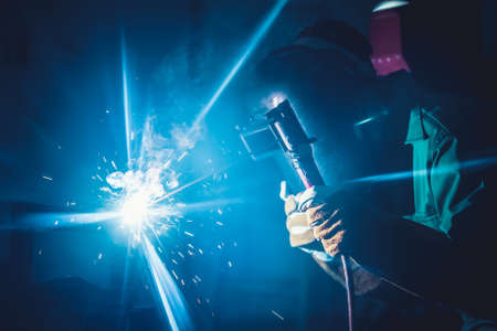 Metal welding steel works using electric arc welding machine to weld steel at factory. Metalwork manufacturing and construction maintenance service by manual skill labor concept. Standard-Bild