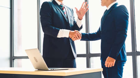 Business people handshake in corporate office showing professional agreement on a financial deal contract. Banque d'images