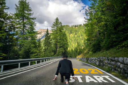 The 2021 New Year journey and future vision concept . Businessman traveling on highway road leading forward to happy new year celebration in beginning of 2021 for fresh and successful start .