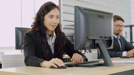 Business people wearing headset working in office to support remote customer or colleague. Call center, telemarketing, customer support agent provide service on telephone video conference call. Zdjęcie Seryjne