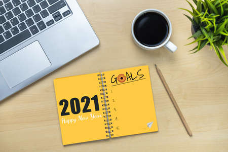 2021 Happy New Year Resolution Goal List - Business office desk with notebook written in handwriting about plan listing of new year goals and resolutions setting. Change and determination concept. Banco de Imagens