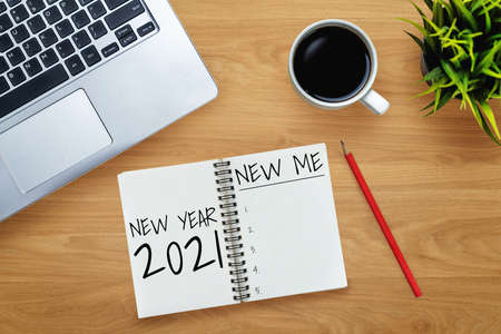 2021 Happy New Year Resolution Goal List - Business office desk with notebook written in handwriting about plan listing of new year goals and resolutions setting. Change and determination concept.