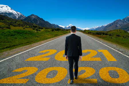 The 2021 New Year journey and future vision concept . Businessman traveling on highway road leading forward to happy new year celebration in beginning of 2021 for fresh and successful start . Banco de Imagens