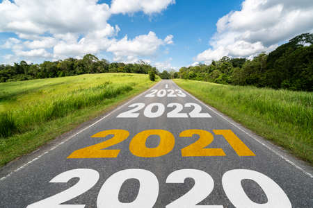 2021 New Year road trip travel and future vision concept . Nature landscape with highway road leading forward to happy new year celebration in the beginning of 2021 for fresh and successful start . Stock Photo
