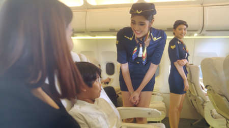 Cabin crew provide service to family in airplane . Airline transportation and tourism concept.