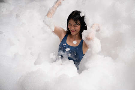 Girl playing in bubble pool with fun and joy . Summer people recreation .