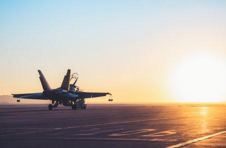 Jet fighter on an aircraft carrier deck against beautiful sunset sky