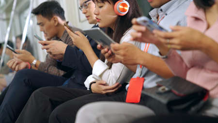 Young people using mobile phone in public underground train . Urban city lifestyle and commuting in Asia concept . 免版税图像