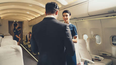 Cabin crew greeting passenger in airplane . Airline transportation and tourism concept.
