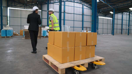 Factory workers deliver boxes package on a pushing trolley in the warehouse . Industry supply chain management concept . Banque d'images