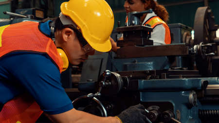Group of skillful workers using machine equipment in factory workshop . Industry and engineering people technology concept .