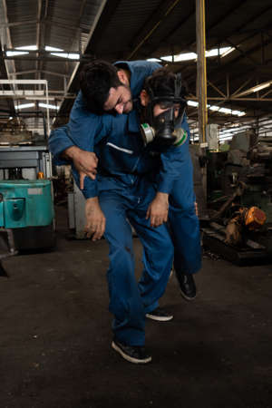 Skillful factory worker rescue his teammate out of poisonous gas leakage . Industry and engineering people accident and safety concept .