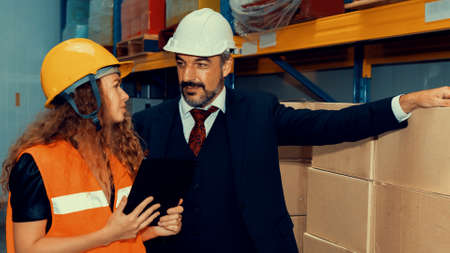 Warehouse senior manager discuss with worker in the storehouse . Logistics , supply chain and warehouse business concept .