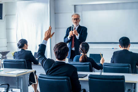 Senior leader speaker speaks to public people audience in training workshop or conference. Mature lecturer is CEO executive manager leading the symposium event. International business seminar concept.