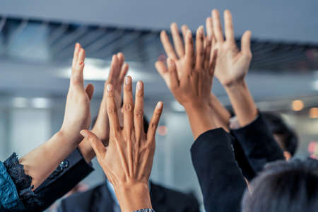 Many happy business people raise hands together with joy and success.