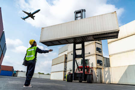 Young African American woman worker at overseas shipping container yard . Logistics supply chain management and international goods export concept . Stock Photo