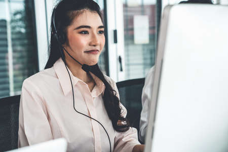 Businesswoman wearing headset working actively in office . Call center, telemarketing, customer support agent provide service on telephone video conference call.