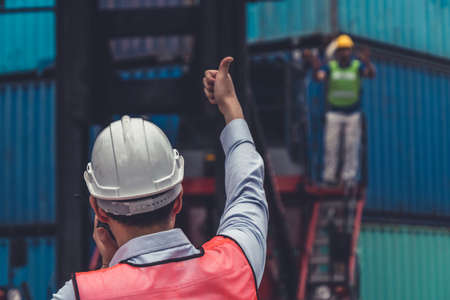 Industrial worker works with co-worker at overseas shipping container yard . Logistics supply chain management and international goods export concept .