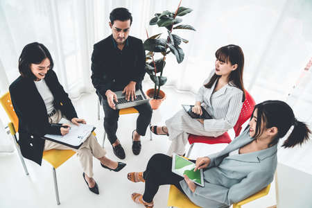 Business people proficiently discuss work project while sitting in circle . Corporate business team collaboration concept .