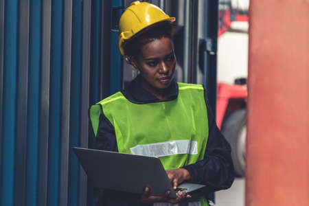 Young African American woman worker at overseas shipping container yard . Logistics supply chain management and international goods export concept . 免版税图像