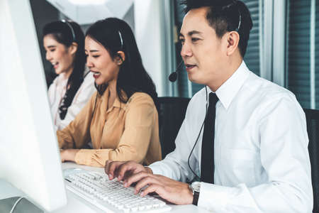 Business people wearing headset working actively in office . Call center, telemarketing, customer support agent provide service on telephone video conference call.