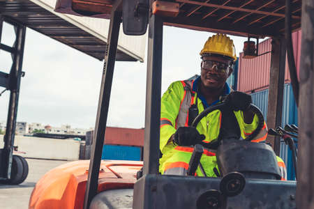 African american man driving forklift in shipyard . Logistics supply chain management and international goods export concept . 免版税图像