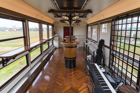 """sake: Niigata, Japón - abril 10,2016: La cabina centro de eventos del tren turístico """"Koshino Shu * Kura"""". Esta cabina tiene sake (vino de arroz) y la barra de alimentos, mesas altas y el rendimiento y el espacio para la música de jazz."""