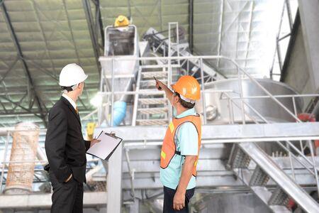 supervisores: Ingeniero y supervisores están comprobando fabricación.